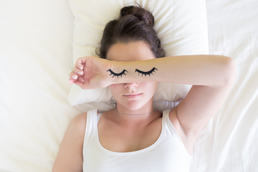 istock Painted sleeping eyes and brunette young woman in the bed at morning time 821296022