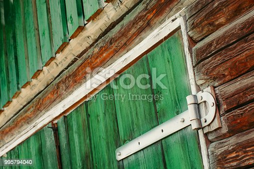 Painted white iron hinges on green wooden gates of shed close up. Textured detailed background with wood planks painted of green paint with copy space. Rotated composition of barn. Rustic construction