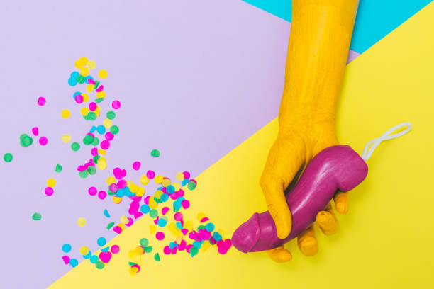 painted yellow hand holds purple soap in the shape of male body part on geometry background with confetti. - human sperm stock pictures, royalty-free photos & images