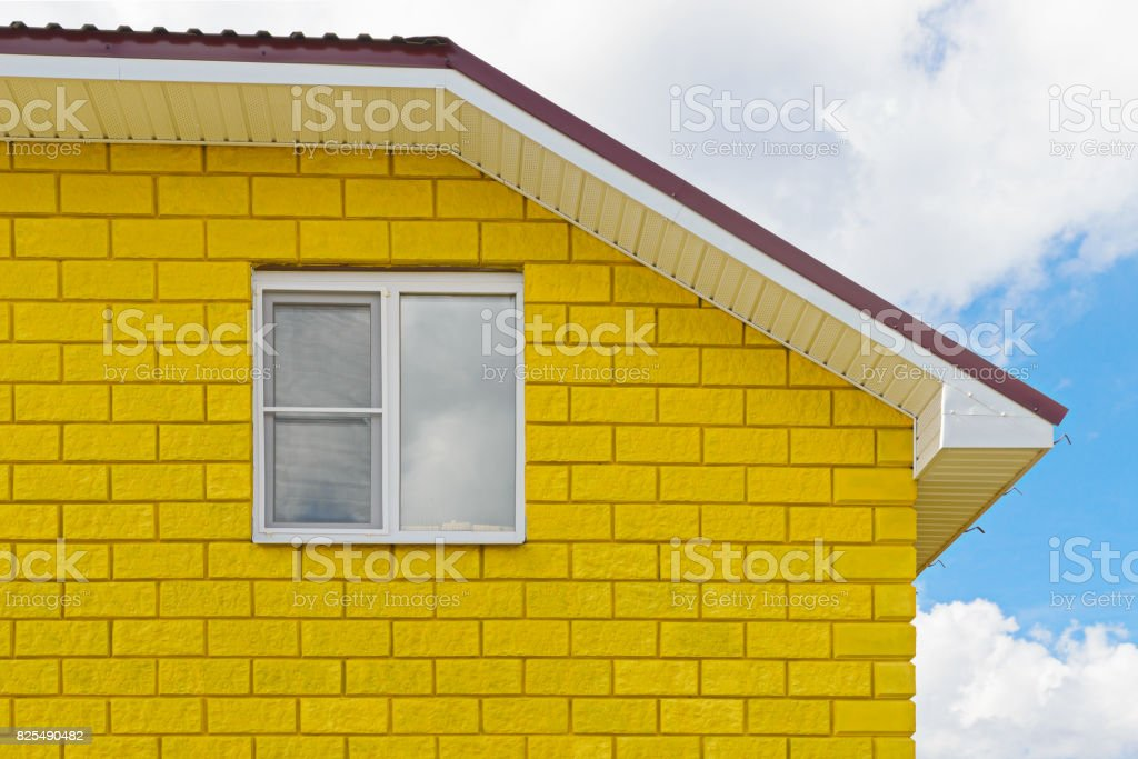 Painted yellow wall of blocks with a window stock photo