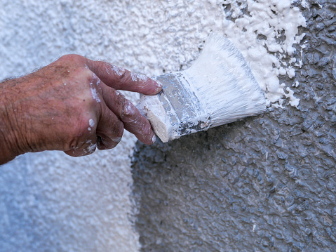 A painter and decorator painting new roughcast, pebbledash