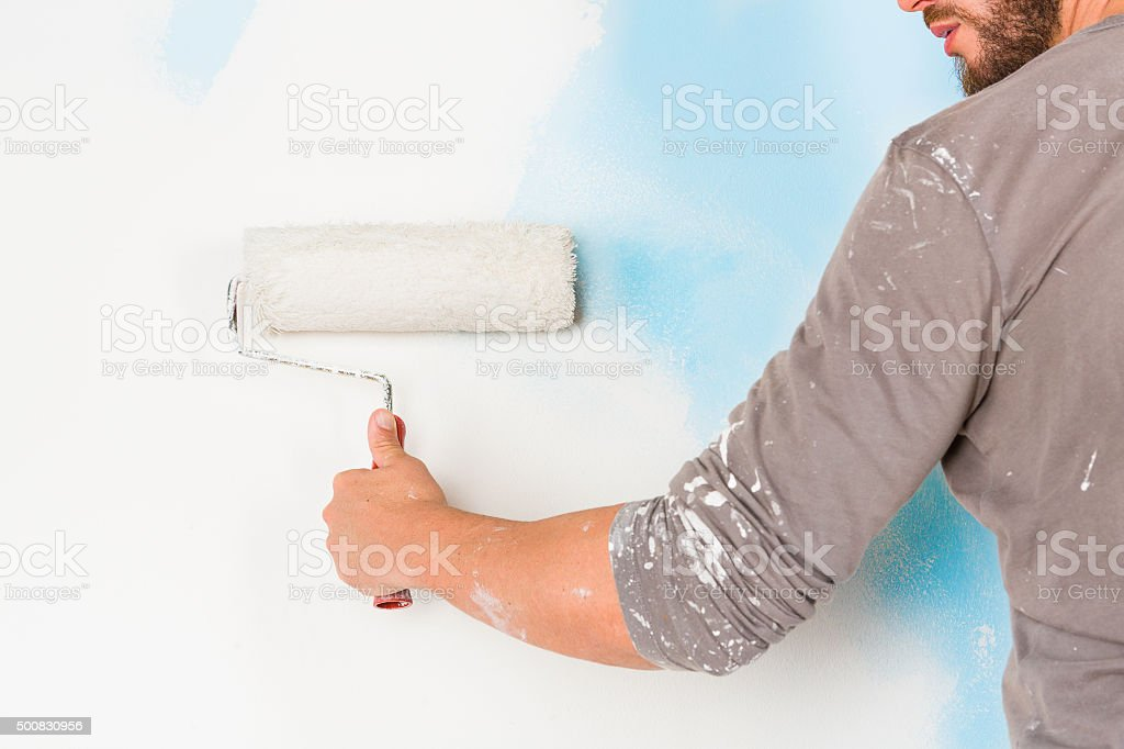 painter arm painting a wall with paint roller stock photo