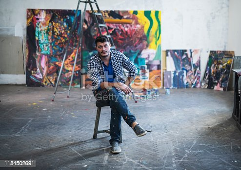 Portrait of young artist painter sitting in front on his big modern paintings in art studio.