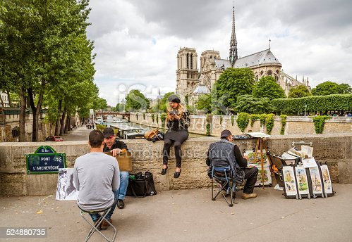 Paris, France - May 29, 2014: Man sitting having his portrait done by a male artist at Pont de la Tournelle, famous Notre Dame church in the background.