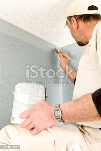 A painter is cutting in a wall to the ceiling area.