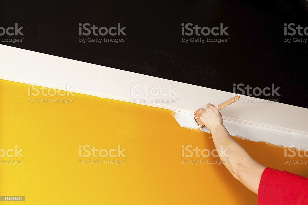 Painter Cutting In White Paint next to Trim Board royalty-free stock photo