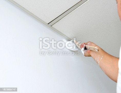 Painter is cutting in wall to the Ceiling