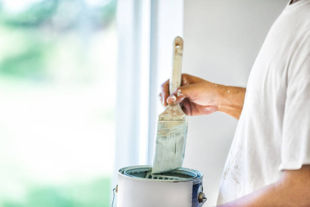 painter dipping his brush in paint can - painter stock photos and pictures