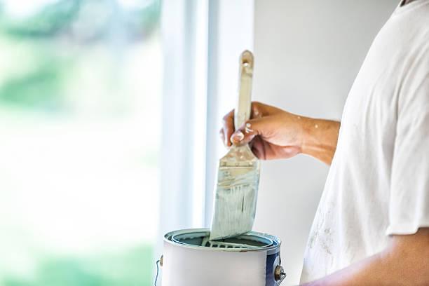 Maler dipping seine Pinsel mit Farbe kann – Foto
