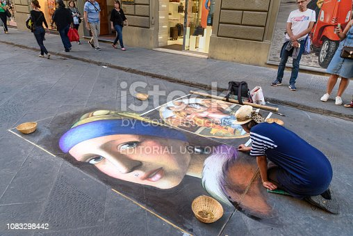 istock Painter drawing picture with chalk on asphalt in the street in Florence. Italy 1083298442