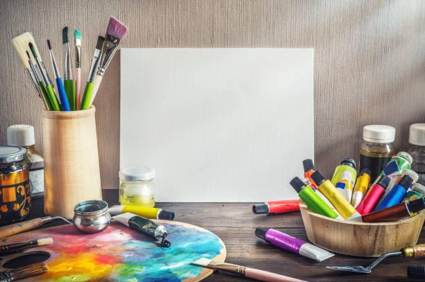 Painter equipment in a artist studio: empty canvas, tube of oil paint, art brushes, palette knife lying.  Artist workshop background. stock photo