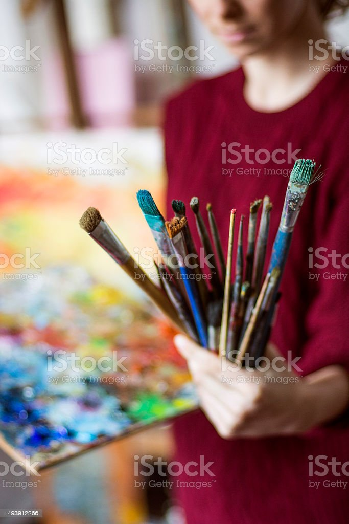 Painter holding bunch of brushes stock photo