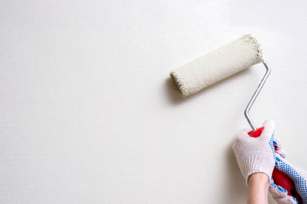 painter holds the roller at the white walls stock photo