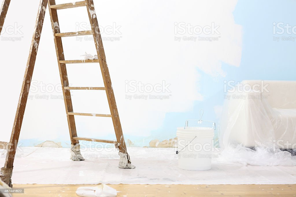 painter house concept, wooden ladder, bucket, and white wall stock photo