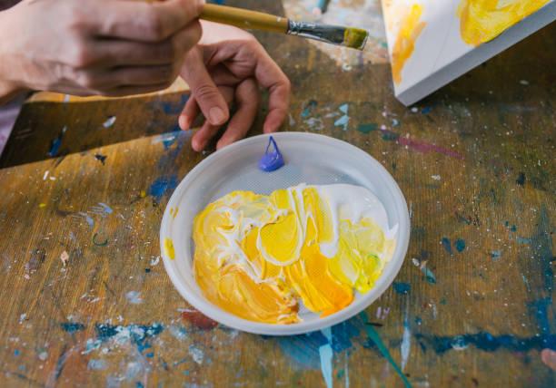 maler in seiner hand halten pinsel gemischte farbe ölfarben für die malerei auf palette. - handbemalte teller stock-fotos und bilder