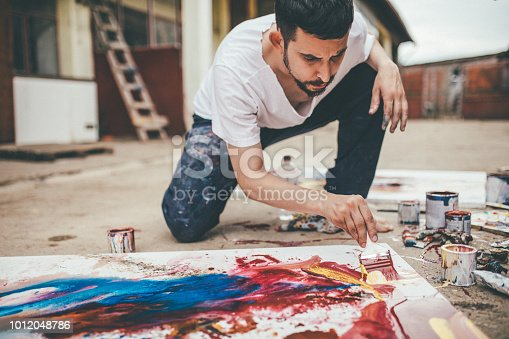 One man, young artist painting on the floor in his back yard outdoors.