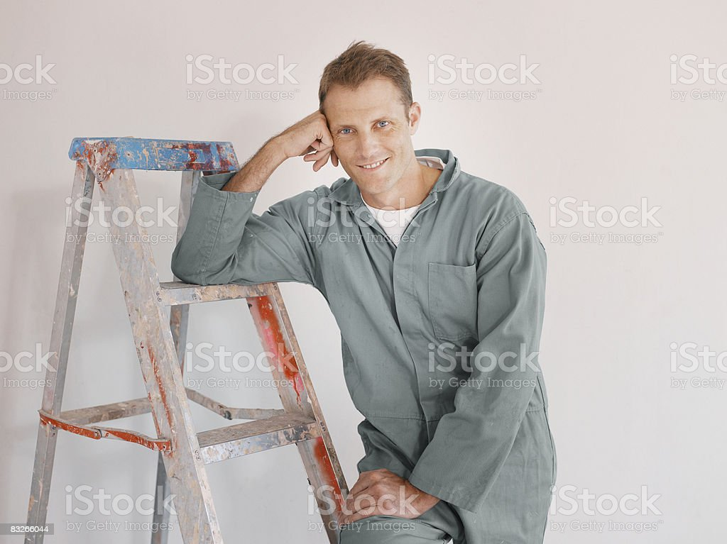 Painter in overalls leaning on ladder royalty free stockfoto