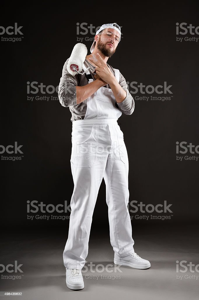 painter in white dungarees and hat standing with paint roller stock photo