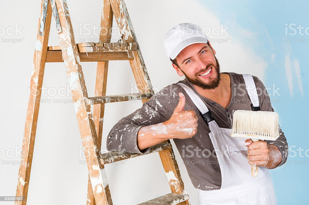 painter in white dungarees with thumbs up gesture stock photo