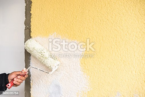 835790922istockphoto Painter is painting wall new with paint roller 865035754