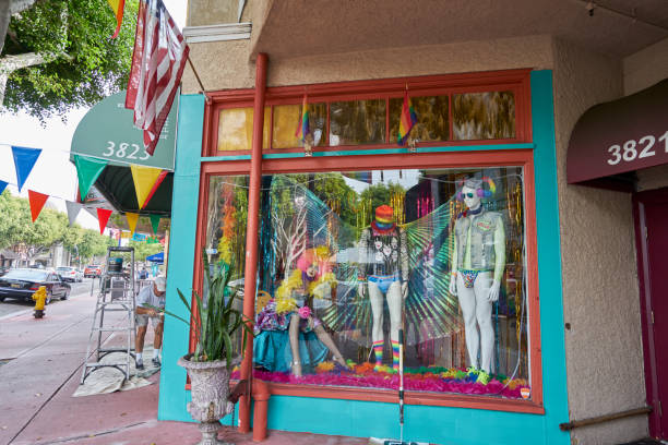 painter is putting finishing touches on local clothing boutique for LGBT Pride Celebration stock photo