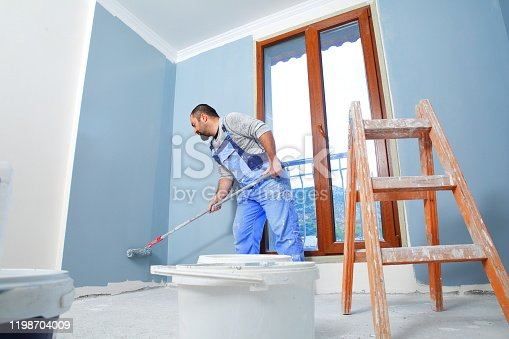 Painter man at work takes the color with paint roller from the bucket. With copy space