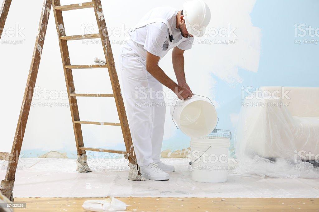 Pintor homem no trabalho despeje no balde de cores - foto de acervo