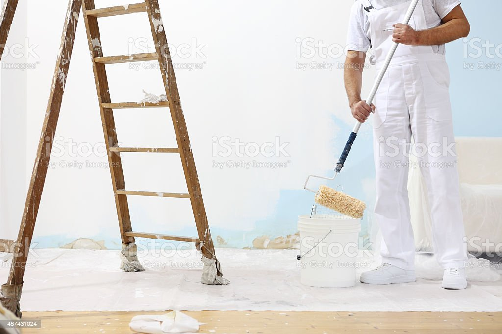 painter man at work takes the color with paint roller stock photo