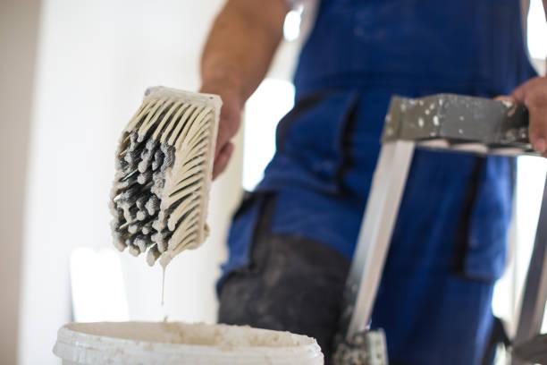 schilder man aan het werk met een emmertje, muurschildering concept - flat cap stockfoto's en -beelden