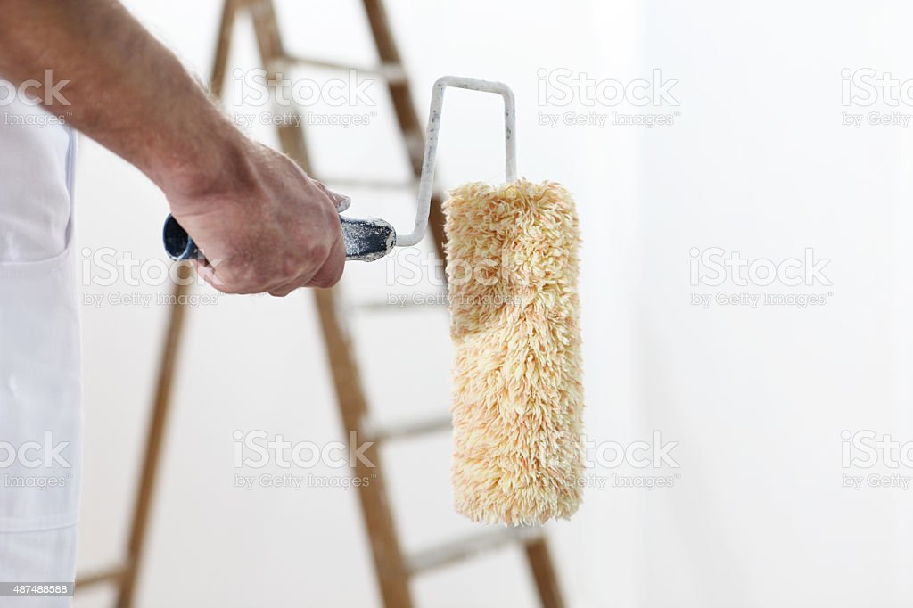 painter man at work with a paint roller and ladder stock photo