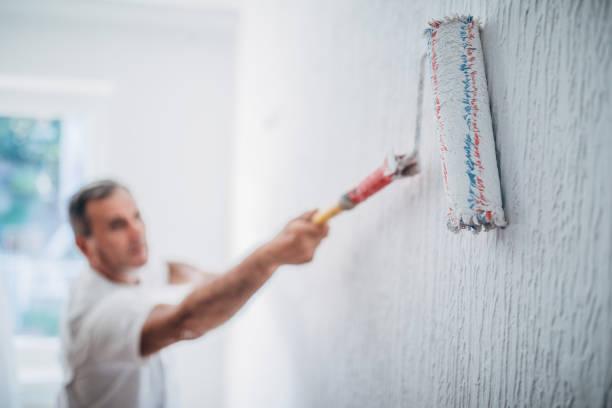 maler mann bei der arbeit mit einer farbwalze - künstler stock-fotos und bilder