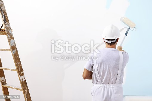 istock painter man at work with a paint roller 487542800