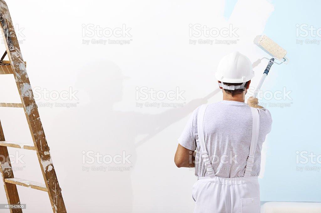 Peintre l'homme au travail avec un rouleau à peinture - Photo
