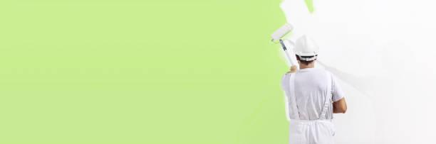 hombre de pintor en el trabajo con rodillo de pintura, concepto ecológico de color verde de la pintura de pared, plantilla de banner web - pintor fotografías e imágenes de stock