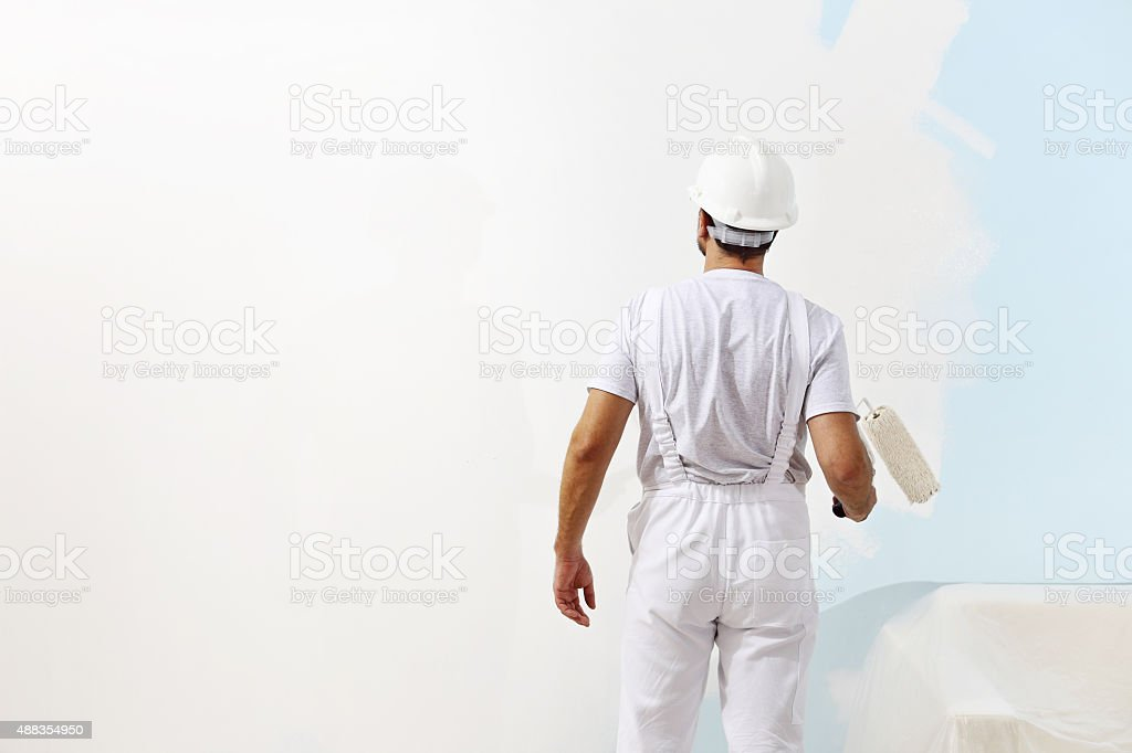 painter man at work with a paint roller, wall painting stock photo