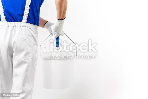589454570 istock photo painter man at work with paint roller from the bucket 494666906