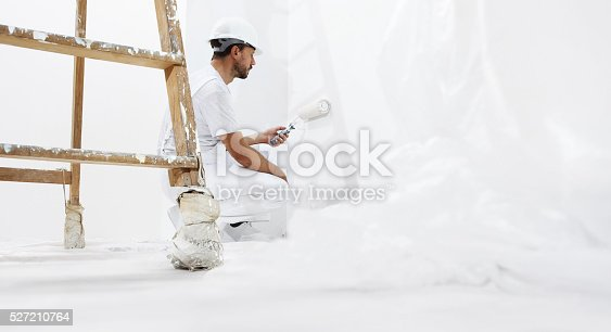 istock painter man at work with paint roller the wall 527210764