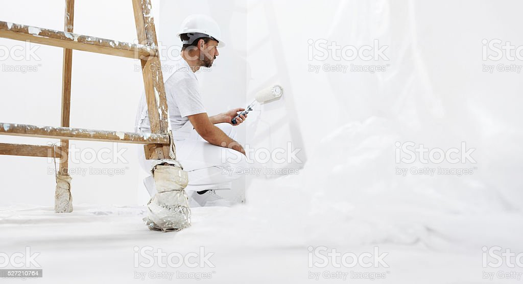 painter man at work with paint roller the wall stock photo