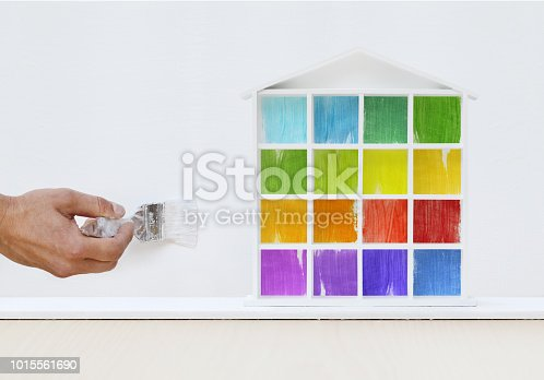 istock painter man hand with paint brush painting colored house model on wall, home service concept, blank banner template with copy space 1015561690