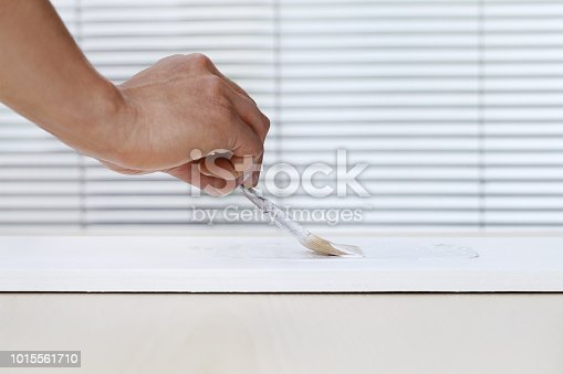 istock painter man hand with paint brush painting on white board, house service concept, blank banner template with copy space 1015561710