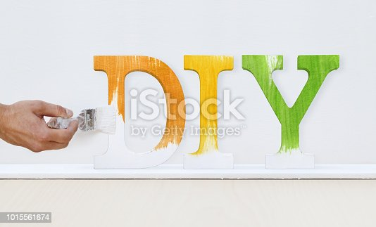 istock painter man hand with paint brush painting text diy on white board, house service concept, blank banner template with copy space 1015561674
