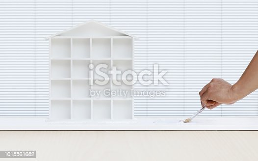 istock painter man hand with paint brush painting white house model on board, home service concept, blank banner template with copy space 1015561682