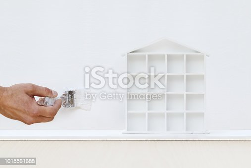 istock painter man hand with paint brush painting white house model on board, home service concept, blank banner template with copy space 1015561688
