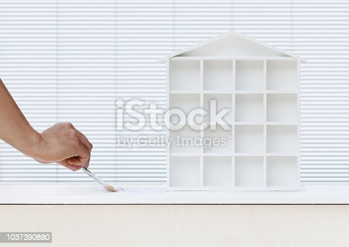 istock painter man hand with paint brush painting white house model on board, home service concept, blank banner template with copy space 1037390880
