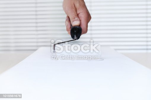 istock painter man hand with paint roller, painting on white board background, house service concept 1015561676