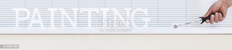 istock painter man hand with paint roller painting text on white board, house service concept, blank banner template with copy space 1015561692