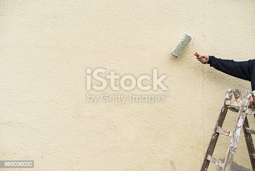 835790922istockphoto Painter man on ladder with paint roller working on exterior wall 865036032