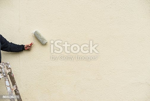 835790922istockphoto Painter man on ladder with paint roller working on exterior wall 865036220