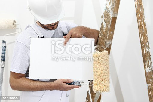 istock painter man showing blank white sign, with paint roller and ladder 687166662