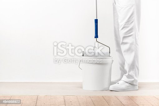 istock Painter man takes the color with paintroller from the bucket 494668922